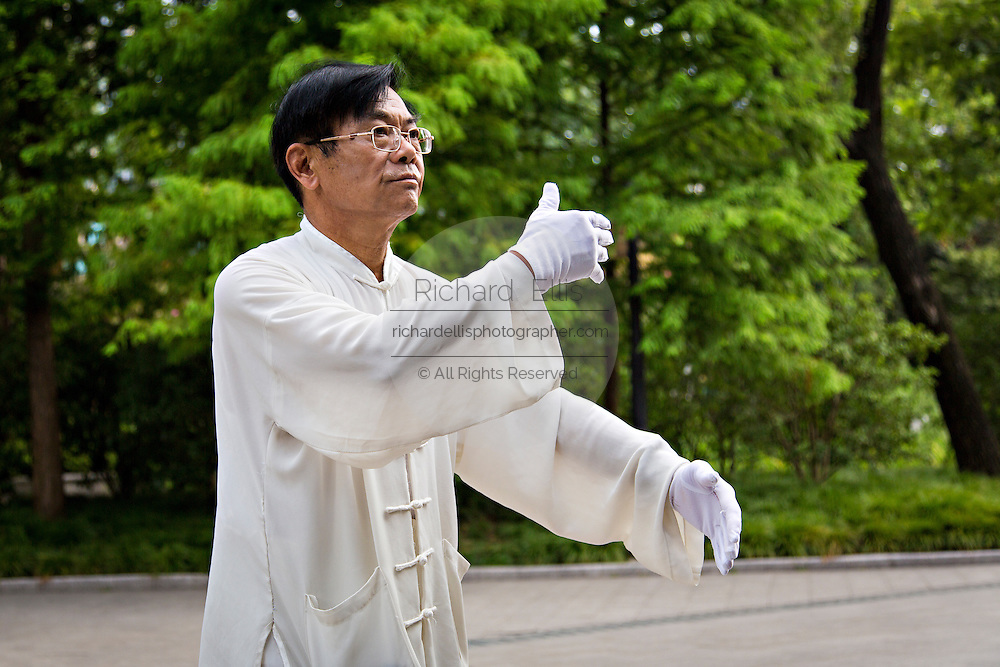 An elderly man exercises in Fuxing Park Shanghai, China