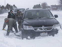 April 14, 2018 - Valentine, Nebraska, U.S. - DJ BROMLICH, foreground, attempts to help free a Dodge Journey SUV that got stuck in a snowdrift for SHELBY BUECHEL, background right, and her friend KAYLIN RISER, background left. A historic late season blizzard struck the Northern Plains Friday and Saturday with storm total accumulations ranging from 1-2 feet and sustained winds of 35-45 mph with gusts in excess of 60 mph, closing dozens of roads including Interstate 80. Nebraska Governor Ricketts declared a state of emergency. (Credit Image: © Mark 'Storm' Farnik via ZUMA Wire)