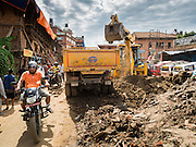 02 AUGUST 2015 - BHAKTAPUR, NEPAL:   A man in Bhaktapur rides his motorcycle past a crew removing debris from the earthquake that hit Nepal in April 2015. Bhaktapur was badly damaged in the earthquake the hit Nepal in April 2015. The Nepal Earthquake on April 25, 2015, (also known as the Gorkha earthquake) killed more than 9,000 people and injured more than 23,000. It had a magnitude of 7.8. The epicenter was east of the district of Lamjung, and its hypocenter was at a depth of approximately 15km (9.3mi). It was the worst natural disaster to strike Nepal since the 1934 Nepal–Bihar earthquake. The earthquake triggered an avalanche on Mount Everest, killing at least 19. The earthquake also set off an avalanche in the Langtang valley, where 250 people were reported missing. Hundreds of thousands of people were made homeless with entire villages flattened across many districts of the country. Centuries-old buildings were destroyed at UNESCO World Heritage sites in the Kathmandu Valley, including some at the Kathmandu Durbar Square, the Patan Durbar Squar, the Bhaktapur Durbar Square, the Changu Narayan Temple and the Swayambhunath Stupa. Geophysicists and other experts had warned for decades that Nepal was vulnerable to a deadly earthquake, particularly because of its geology, urbanization, and architecture.      PHOTO BY JACK KURTZ