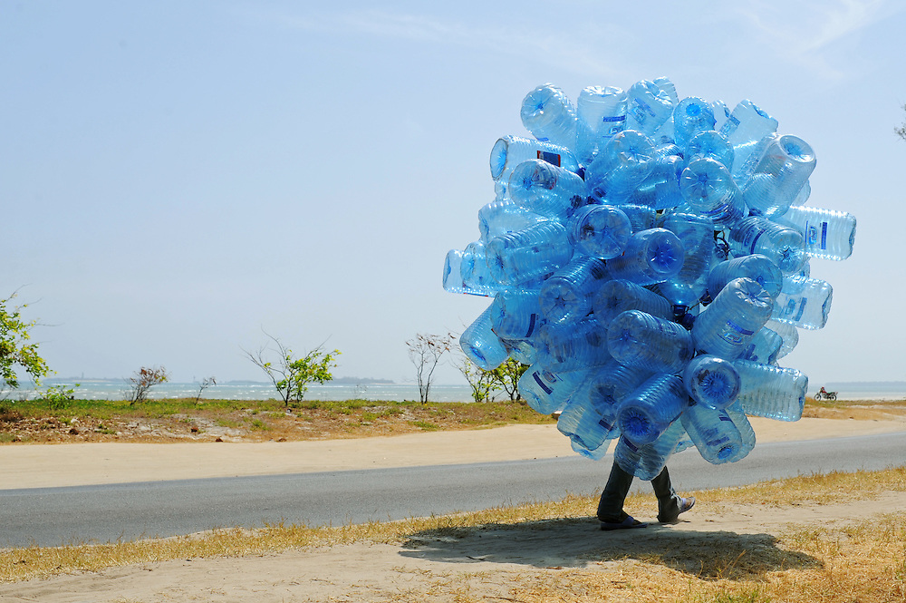 A bottle collector walks along Ocean Road, now known as Barack Obama Drive, in Dar es Salaam, Tanzania on February 4, 2014. Photo by Daniel Hayduk