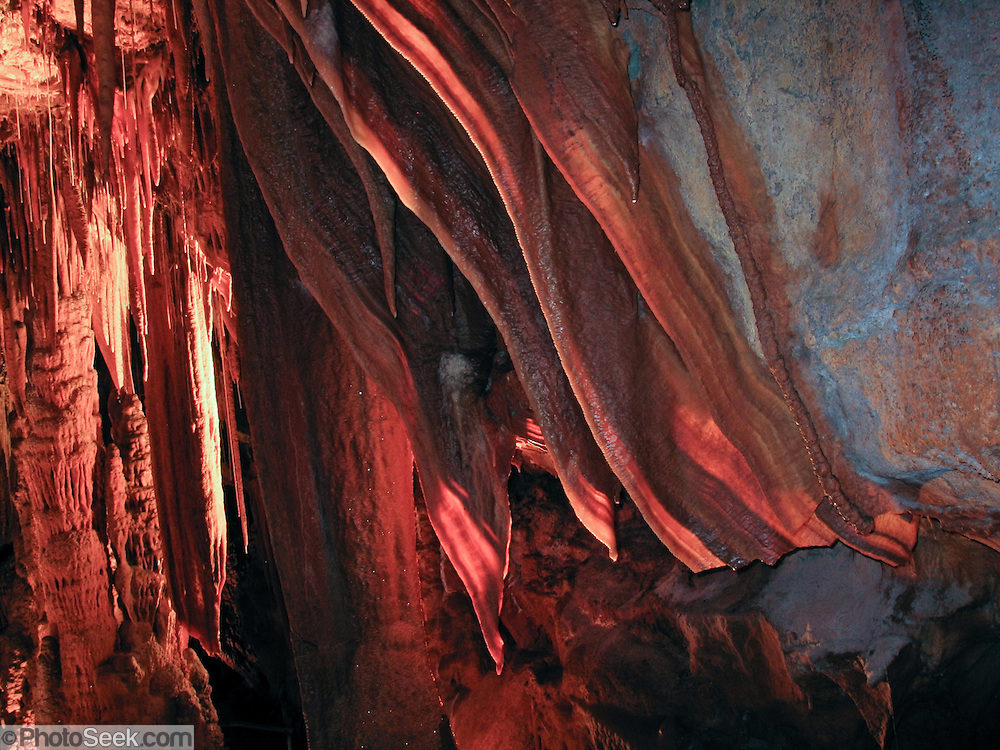 Shawl, stalactite, column, and stalagmite features have formed in the dry King Solomons Cave, in Mole Creek Karst National Park (established 1996), Tasmania, Australia. The park protects over 300 known caves and sinkholes, 168 km northwest of Hobart. Mole Creek Karst National Park is part of the Tasmanian Wilderness honored by UNESCO as World Heritage Site in 1982, expanded in 1989.
