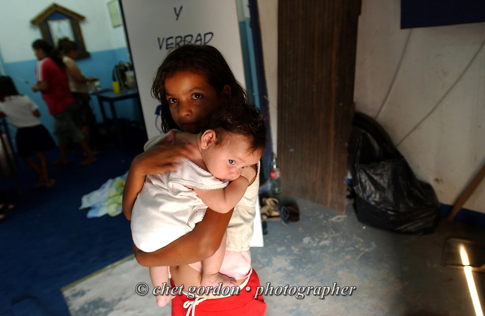 ASUNCION, PARAGUAY.  Young Paraguayan street girl holds a baby in the Asociacion Cultural Justicia y Verdad (Association of Cultural Justice and Truth) in Asuncion, Paraguay on Friday evening, March 17, 2006. The shelter founded by Dr. Chantal Hulin, is run out of a renovated auto garage, where volunteers provide showers, administer health care, simple meals, and classroom activities to some of the hundreds of homeless street children that panhandle and clean windshields for money on the neighborhood streets.
