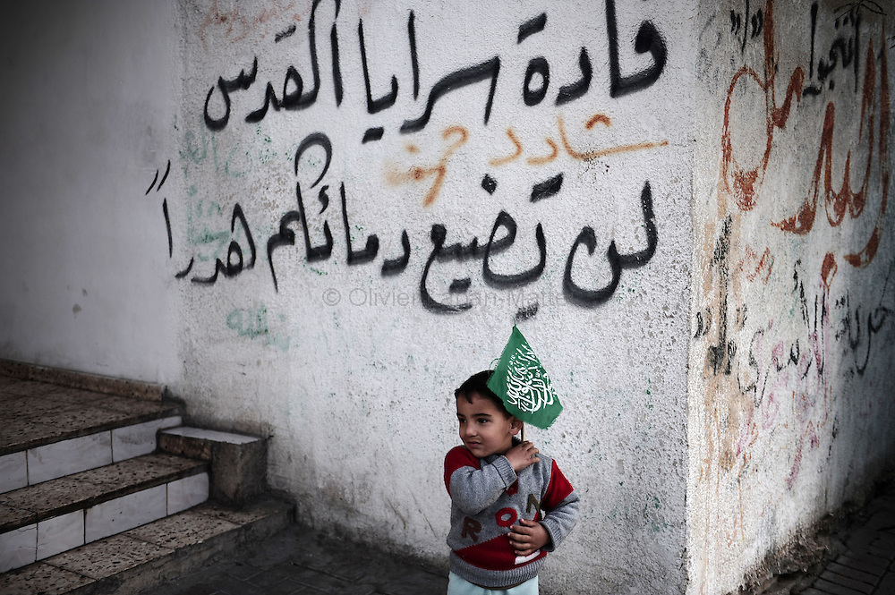 A Palestinian boy plays with a Hamas flag on January 29, 2009 in a street of Gaza city. US envoy George Mitchell called for a durable truce in Gaza as spiralling violence threatened to shatter ceasefires that ended a devastating war in the Hamas-run enclave.