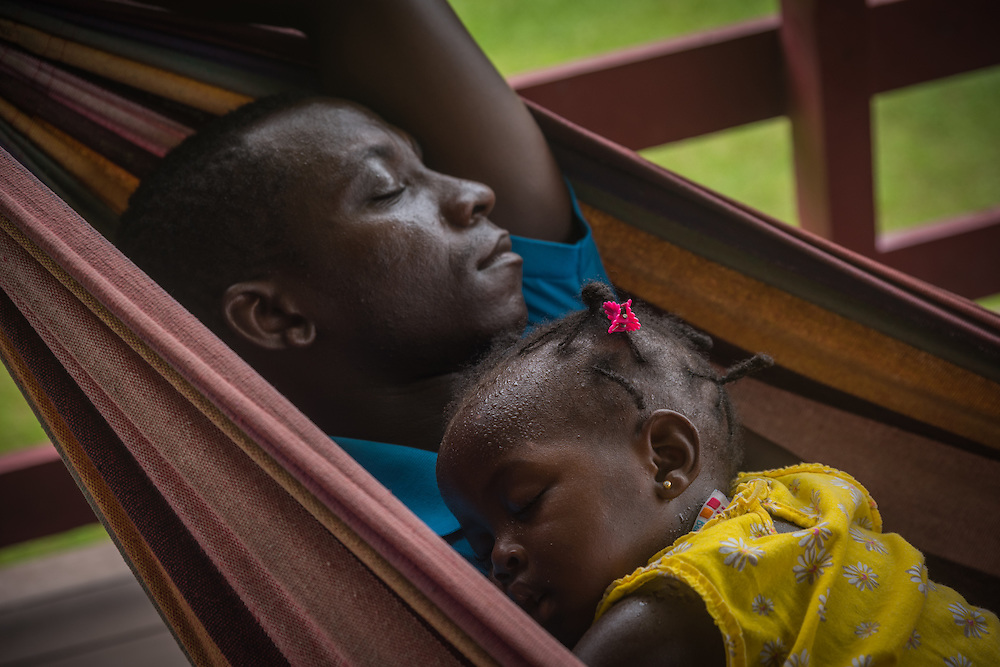 A father is sleeping in a hammock with his daughter, Botopasi, Surinam.