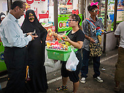 06 JULY 2011 - BANGKOK, THAILAND: An Arab couple buys souvenirs from a Thai vendor in the Soi Arab neighborhood of Bangkok. Soi Arab is an alleyway in Bangkok. What started as an alley has now grown into a neighborhood that encompasses several blocks of restaurants, hotels and money exchanges that cater to Middle Eastern visitors to Thailand. The official name of the street is Sukhumvit Soi 3/1, located in North Nana between Sukhumvit Soi 3 and Sukhumvit Soi 5, not far from the Nana Plaza night-life area and the Grace Hotel popular among Arabs.   PHOTO BY JACK KURTZ