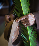 A member of  Our Lady of the Star of the Sea Church leaves church with a palm on Palm Sunday. ©Kathy Anderson, All Rights Reserved
