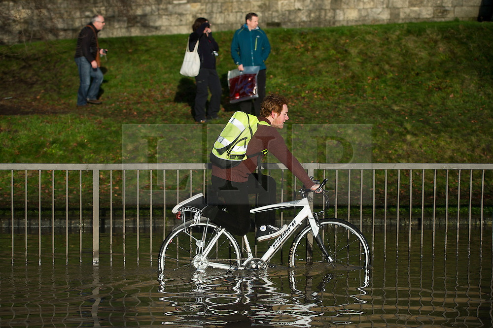 © Licensed to London News Pictures. 27/12/2015. York, UK.  A man rides his bike through flood water in York city centre. Large areas of the North of England have been hit by severe flooding following unusually heavy rainfall in December. Photo credit: Ben Cawthra/LNP