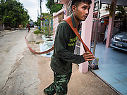14 JULY 2015 - THAILAND: A Thai soldiers runs hose for water deliveries to a home in Pathum Thani province near Bangkok. The drought that has crippled agriculture in central Thailand is now impacting residential areas near Bangkok. The Thai government is reporting that more than 250,000 homes in the provinces surrounding Bangkok have had their domestic water cut because the canals that supply water to local treatment plants were too low to feed the plants. Local government agencies and the Thai army are trucking water to impacted communities and homes. Roads in the area have started collapsing because of subsidence caused by the retreating waters. Central Thailand is contending with drought. By one estimate, about 80 percent of Thailand's agricultural land is in drought like conditions and farmers have been told to stop planting new acreage of rice, the area's principal cash crop.       PHOTO BY JACK KURTZ