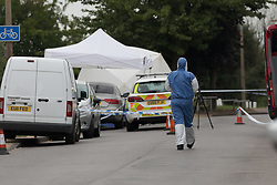 © Licensed to London News Pictures. 01/07/2017. GRAYS, Essex, UK.  A forensic officer at th police cordon at Blackshots Lane in Grays, Essex. A man has died and three others have life threatening injuries following a street fight in Blackshots Lane, Grays, Essex last night.  Photo credit: Vickie Flores/LNP