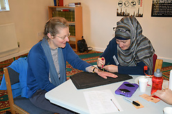 Norwich, UK, 11 November 2017. Open Day at the Rose Lane Mosque, Norwich. Revd Dr Fiona Haworth from The Church of St Peter Mancroft in Norwich having a henna tattoo painted on her hand. This communal event allows the wider community to visit and learn about Islam and the way of life of 5% of the UK population.