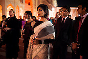 OzFest ambassador Pallavi Sharda (in white saree) wears Argyle Pink Diamond jewelry by Nirav Modi as she stands amongst other guests listening to a speech while sipping pink champagne in front of a jewelry exhibition before a violin recital at the OzFest Gala Dinner in the Jaipur City Palace, in Rajasthan, India on 10 January 2013. Photo by Suzanne Lee