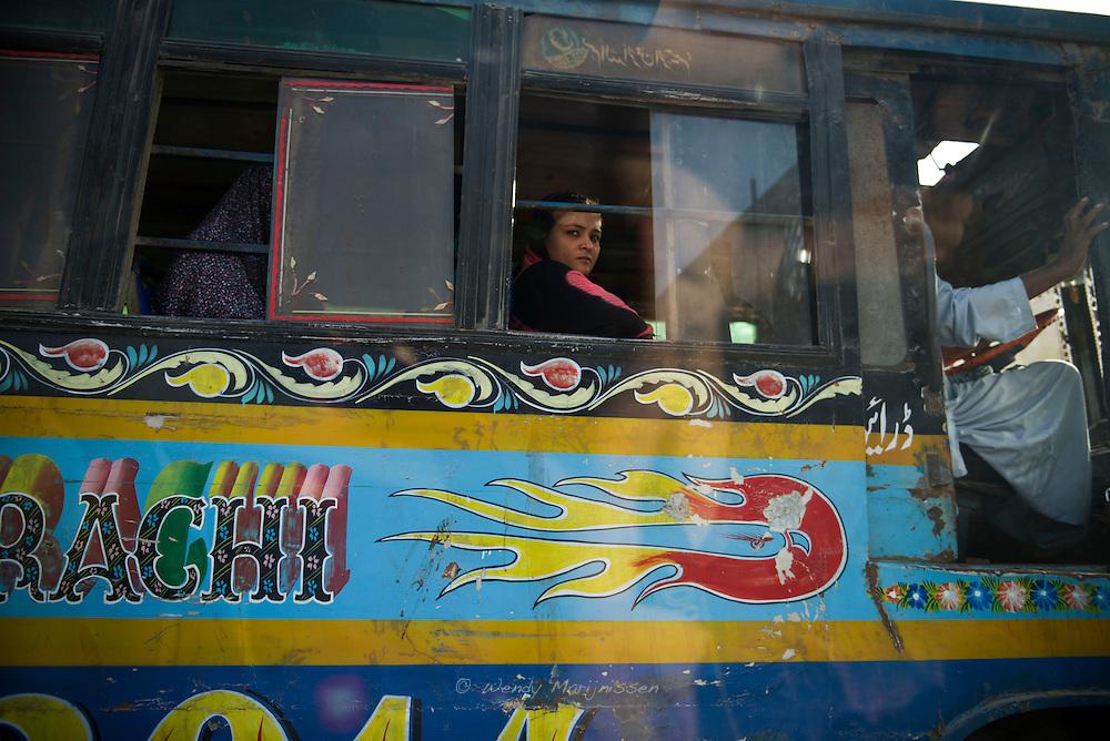 A woman riding the bus, Karachi, Pakistan