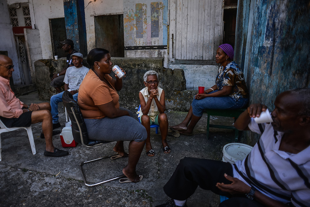 Residents drink beer during a block party outside of the crumbling building where they live in Colón, Panama. Despite being the second largest city in Panama, Colón is one of the poorest in the region, and its residents suffer from a critical shortage of potable water, sewer connections and housing--many people live in condemned or should be condemned buildings. Panama is now one of the fastest growing countries in Latin America and there is a growing resentment and impatience that Colon has not reaped as much of the benefit as Panama City.