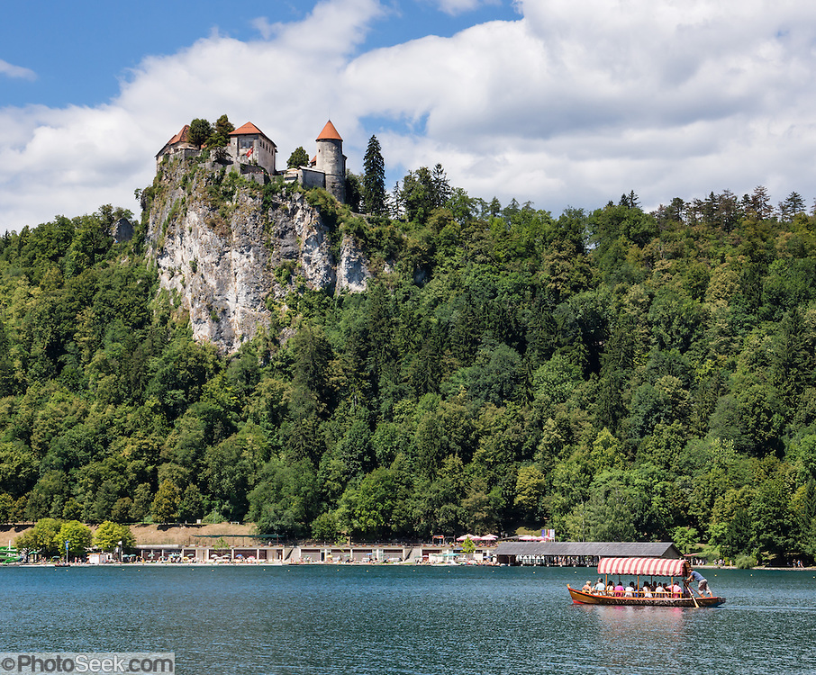 "A Pletna boat paddles across Lake Bled under the medieval Bled Castle (Slovene: Blejski grad, German: Burg Veldes), which was built a little before 1011 AD on a cliff above the city of Bled, in what is now Slovenia, Europe. The distinctive two-paddle Pletna boats originated in 1590 and can carry 20 people. A colourful awning protects passengers from sun and weather. The respected title of ""Pletnarstvo,"" Pletna oarsman, has been handed down within specific families from generation to generation."