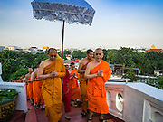 18 NOVEMBER 2015 - BANGKOK, THAILAND:  Buddhist monks lead a procession up Wat Saket during the parade marking the start of the temple's annual fair. Wat Saket is on a man-made hill in the historic section of Bangkok. The temple has golden spire that is 260 feet high which was the highest point in Bangkok for more than 100 years. The temple construction began in the 1800s in the reign of King Rama III and was completed in the reign of King Rama IV. The annual temple fair is held on the 12th lunar month, for nine days around the November full moon. During the fair a red cloth (reminiscent of a monk's robe) is placed around the Golden Mount while the temple grounds hosts Thai traditional theatre, food stalls and traditional shows.       PHOTO BY JACK KURTZ