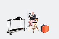 Senior photographer looking at camera while sitting on director's chair in studio