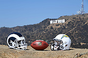 General overall view of Los Angeles Chargers (left) and Los Angeles Rams helmets and NFL official Wilson Duke football with the Hollywood sign and Mount Lee as a backdrop in Los Angeles, Wednesday, Sept. 19, 2018. After more than two decades without an NFL team, the Rams relocated from St. Louis in 2016 and the Chargers moved in 2017. The teams will share a stadium financed by Rams owner Stan Kroenke at the LA Stadium and Entertainment District in Inglewood, Calif. scheduled to be completed in 2020.