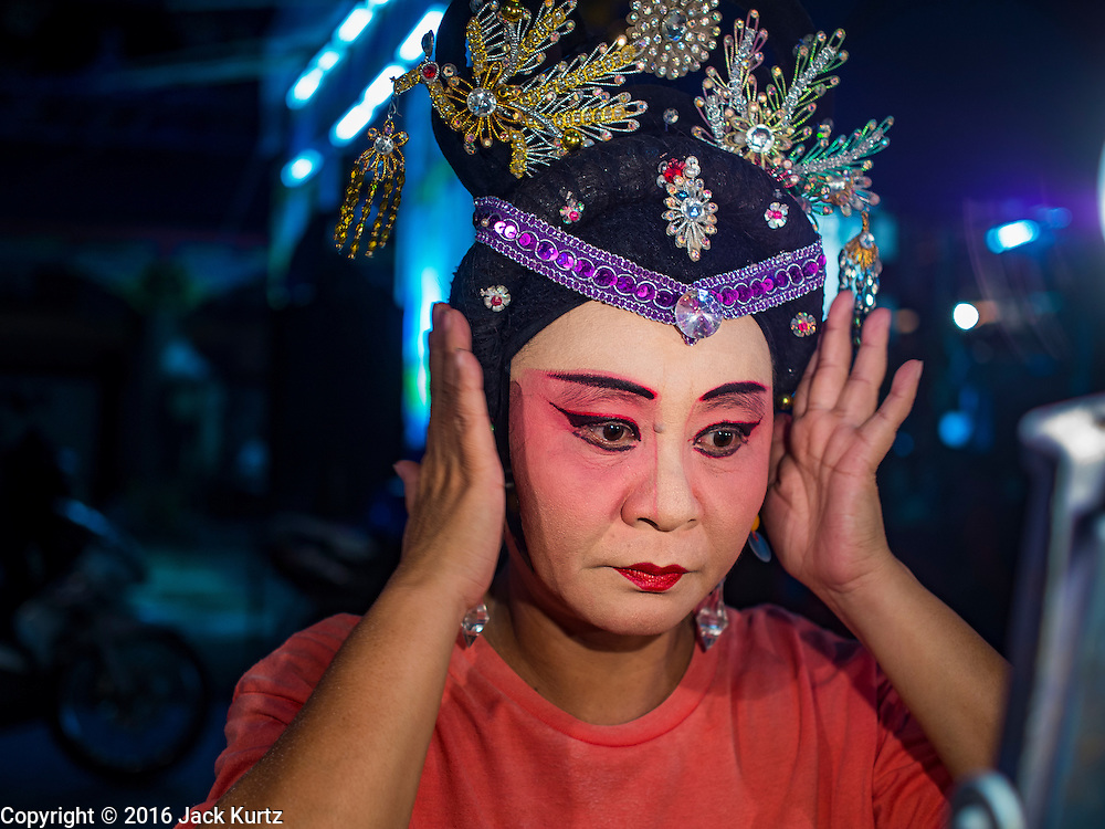 """30 JUNE 2016 - BANGKOK, THAILAND: A performer puts on her costume before a Chinese opera performance at Chiao Eng Piao Shrine in Bangkok. Chinese opera was once very popular in Thailand, where it is called """"Ngiew."""" It is usually performed in the Teochew language. Millions of Chinese emigrated to Thailand (then Siam) in the 18th and 19th centuries and brought their culture with them. Recently the popularity of ngiew has faded as people turn to performances of opera on DVD or movies. There are about 30 Chinese opera troupes left in Bangkok and its environs. They are especially busy during Chinese New Year and Chinese holidays when they travel from Chinese temple to Chinese temple performing on stages they put up in streets near the temple, sometimes sleeping on hammocks they sling under their stage.       PHOTO BY JACK KURTZ"""