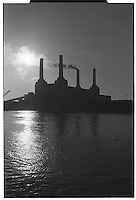 Backlit Battersea power station with one chimney smoking, London street photography in 1982. Tri-X