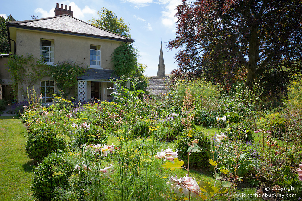 General view of the garden and church at The Old Parsonage with Lilum regale and fennel in the foreground
