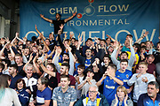 AFC Wimbledon fans singing during the EFL Cup match between AFC Wimbledon and Milton Keynes Dons at the Cherry Red Records Stadium, Kingston, England on 13 August 2019.