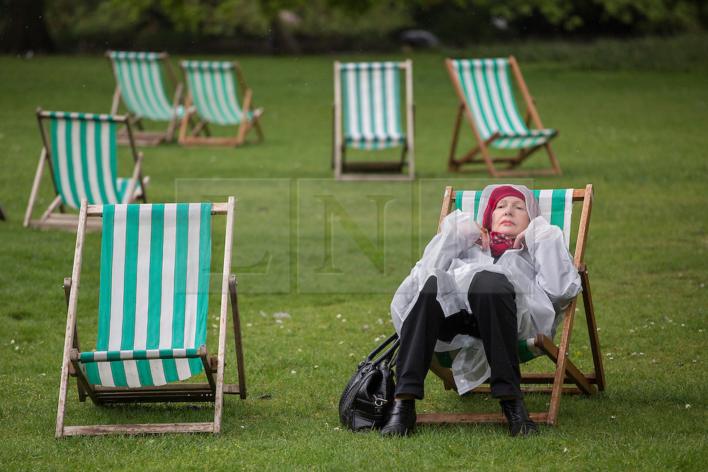 © licensed to London News Pictures. London, UK 09/05/2013. A woman resting on a deckchair under the rain in St James's Park in London on Thursday, 09 May 2013. Photo credit: Tolga Akmen/LNP