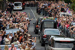© Licensed to London News Pictures. 20/08/2015. Liverpool, UK. Mourners line the street leading to the church as the The funeral cortege carrying the coffin of much loved British  singer and and entertainer Cilla Black arrives at St Mary's Church in Woolton, Liverpool, UK. Cilla black died following a fall at her holiday hoe in Estepona, Spain earlier this month. Photo credit: Ben Cawthra/LNP