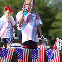 Olivia Anderson, 6, of Tupelo, stands in the family's parade float as she gets a cool drink prior to the start of the Joyner Neighborhood Fourth of July Parade Wednesday morning in Tupelo.