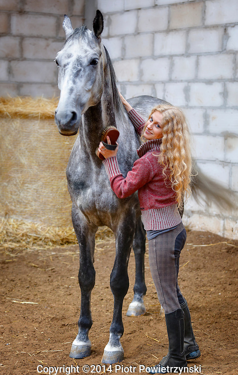 Beautiful young woman grooming horse.