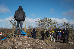 Licensed to London News Pictures. Calais, France. 03/03/16.  A refugee looks on as police keep people away from the demolition area. French authorities are clearing the southern half of the Calais 'Jungle' camp, which charities estimate to contain 3,500 people.. Photo credit : Rob Pinney/LNP