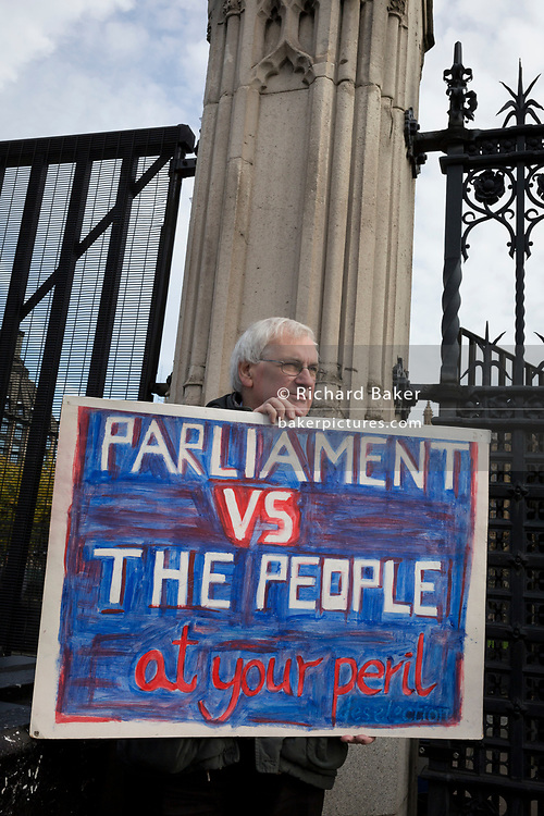 On the day that the EU in Brussels agreed in principle to extend Brexit until 31st January 2020 (aka 'Flextension') and not 31st October 2019, a Brexiter's stands beneath the railings outside parliament with a placard warning of a confrontation between the People and Parliament, on 28th October 2019, in Westminster, London, England.