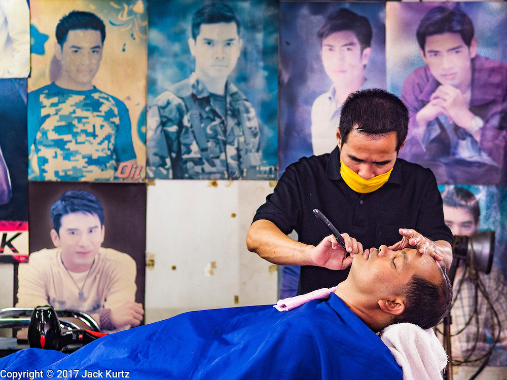 """06 FEBRUARY 2017 - BANGKOK, THAILAND: A barber gives a customer a shave in a small barbershop in what used to be known as Kalabok Market under the Phra Khanong Bridge in the Phra Khanong district of Bangkok. Kalabok is the Thai word for hairdresser and the market was called Kalabok because there were many barbershops and hairdressers under the bridge. In 1985, the city changed the name of the market to """"Singha Market."""" There are still about 10 small men's barbershops, most with just one barber, and four women's salons, most with one hairdresser,  under the bridge.      PHOTO BY JACK KURTZ"""