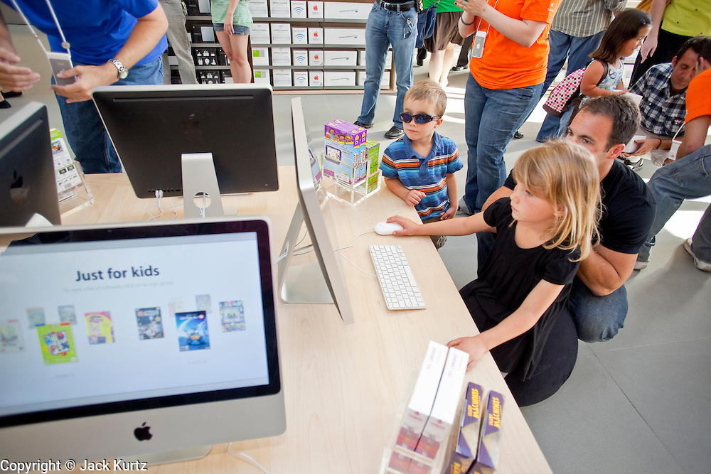 12 JUNE 2009 -- SCOTTSDALE, AZ: People use some of the iMacs in the new Apple Store in Scottsdale, AZ, during the store's grand opening. The outlet will be Arizona's largest Apple Store, occupying nearly 10,000 square feet in the Outdoor Lifestyle Center in the Scottsdale Quarter. The store, the fifth in the Phoenix area, uses a radically different design from other Apple Stores in some respects. Ceilings in the building are approximately 20 feet high, and lined with a 75-foot long skylight, reducing dependence on artificial lighting. Aiding the skylight is an all-glass front and rear, permitting visitors to see directly through the store. More than one thousand people lined to get into the store during the grand opening. Photo by Jack Kurtz