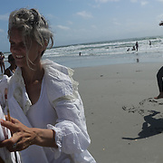 Karola Luttringhaus, left, paints as Courtney Owen-Muir dances during the SARUS Festival Sunday August 24, 2014 at Wrightsville Beach, N.C. (Jason A. Frizzelle)