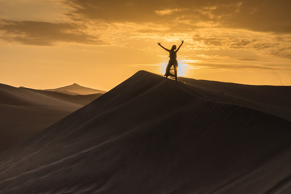 Woman cheers on top of a sanddune at sunset near the town of Huacachina, Peru.