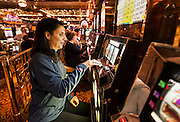 Woman plays casono slot machine.