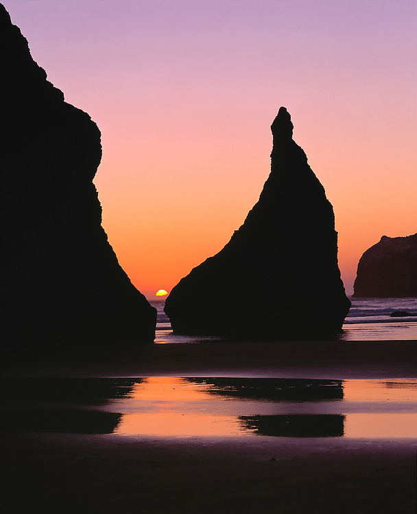 The sun peeks through seastacks as it sets at Face Rock Wayside, Oregon.