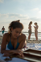 "An Israeli woman plays backgammon (""shesh besh"" in Israel) late on a Saturday afternoon at the beach in Tel Aviv. Two young ladies are in the backround, one texting on her phone."