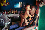 A father and his baby in his house of Port-au-Prince, Haiti.