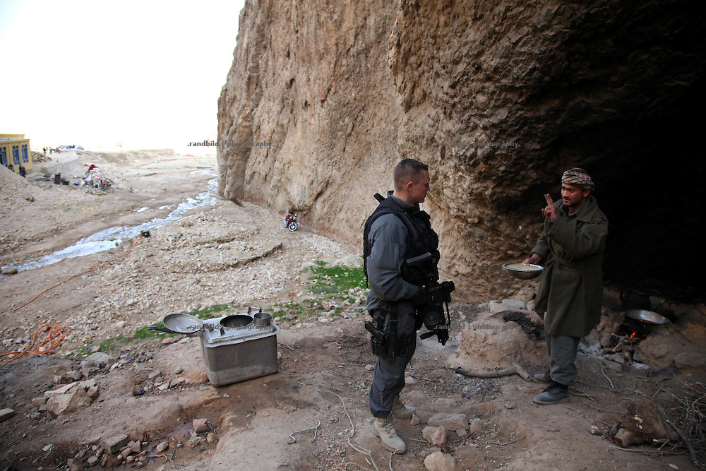 """A german police officer speaks to an afghani man. ..A joint patrol of german military police and civil german police in the Marmal mountain range near Mazar-e Sharif. These """"show of forces"""" patrols are part of the """"Focused District Development""""-Programm which metors afghan police."""