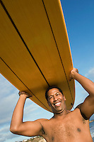 Man Carrying Surfboard on Head