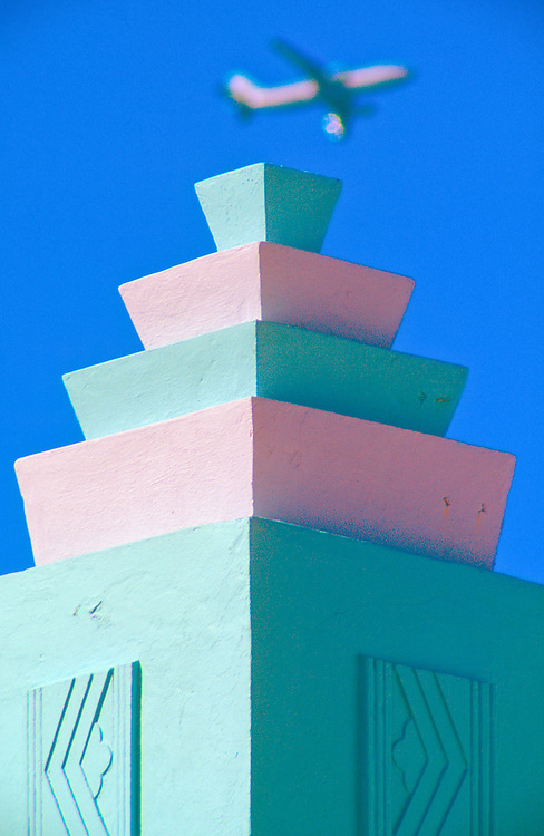 A contmporary jetliner soars over a decorative tower on Miami Beach's  Art Deco-style MacArthur Hotel, designed by architect T. Hunter Henderson in 1930.<br />