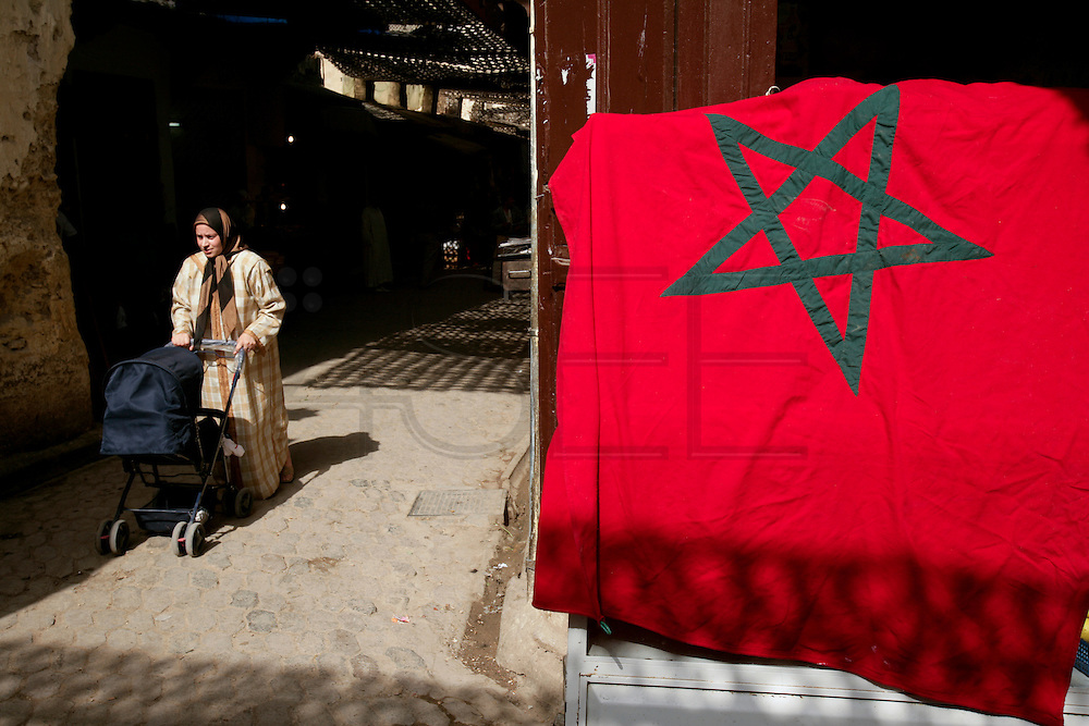 Woman pushing a baby's car near a Moroccan national flag inside Fez Medina.