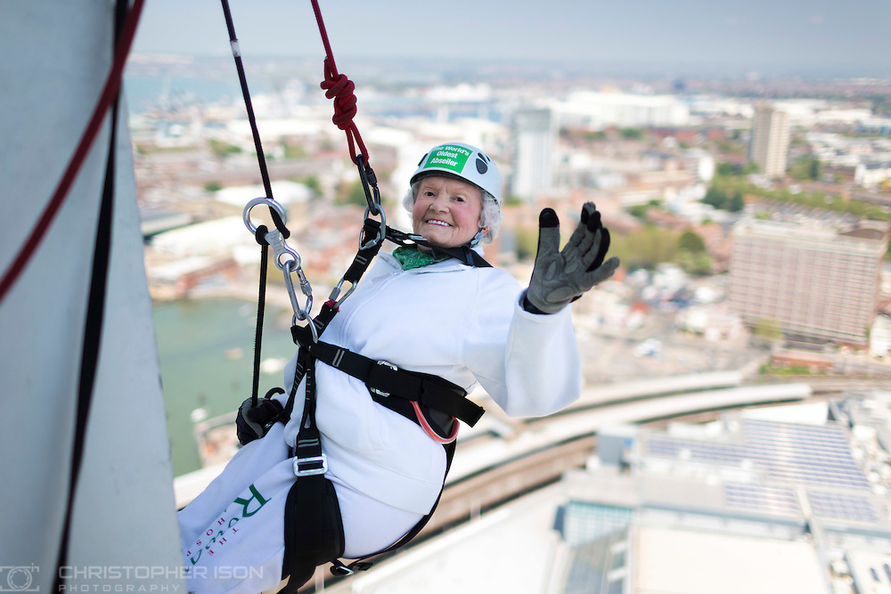 Intrepid centenarian Doris Long MBE waves before abseiling down the 130 metre tall Spinnaker Tower in Portsmouth today, on her 100th Birthday. She performed the feat to raise funds for local charity, The Rowans Hospice and it is her 15th abseil. Daring Doris took up abseiling at 85 and today broke her own record of being the oldest person to abseil. Picture date Sunday 18th May, 2014.<br />