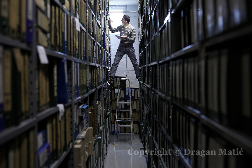 A worker in the Croatian State Archives checks archival material.