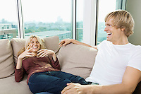 Cheerful couple relaxing on sofa at home