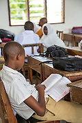 A student reading a book at Mingoyo school. Part of the VSO / ICS Elimu Fursa project (Opportunities in Education) Lindi, Lindi region. Tanzania.