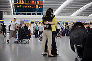 Young lovers say tearful farewells in departures concourse of Heathrow airport's terminal 5.
