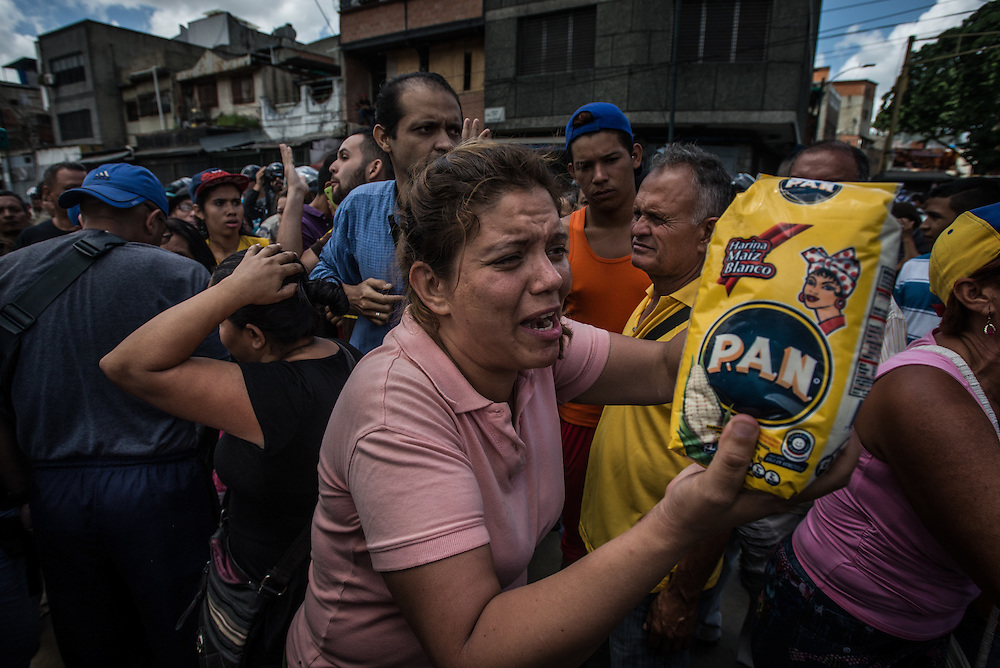 """CARACAS, VENEZUELA - JUNE 11, 2016:  An upset woman fights back tears while shaking a bag of corn flour, a staple of the Venezuelan diet, shouting, """"Why! Why is it so difficult for me to buy this!"""" Hundreds of people waited in line with her to buy food outside of a grocery store in Catia, a slum in western Caracas. The shoppers had arrived as early as 3 am, and waited in line for over eight hours before they were told to go home because there was no more food available for them to buy.  Dozens of people in the line started to protest, exasperated by being told to go home empty handed, after waiting for so long.  When the crowd became unruly, armed """"collectivos"""" of government loyalists arrived and threatened them, beating one man. The protesting shoppers refused to stop, shouting """"we are hungry!"""" until anti-riot police arrived and calmed everyone down.  PHOTO: Meridith Kohut"""