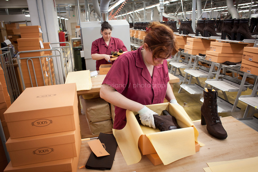 SANT'ELPIDIO A MARE, ITALY - MAY 20: Workers put the finished women shoes in shoe boxes at the factory of the Tod's headquarters in Sant'Elpidio a Mare (FM, Marche), Italy, on May 20, 2011. The Tod's headquarters was designed by Della Valle's wife Barbara Pistilli and was inaugurated in 1998. Tod's Group is an Italian company which produces shoes and other leather goods, and is presided over by businessman Diego Della Valle. It is most famous for its driving shoes.<br /> <br /> Gianni Cipriano for Le Monde
